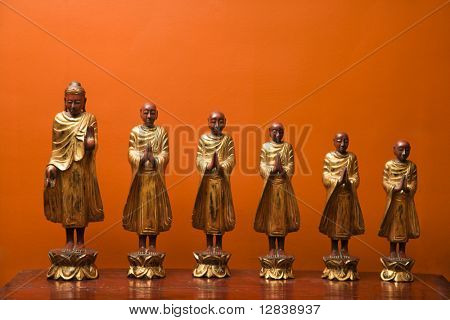 Wooden statues of Buddha with five disciples against orange wall.