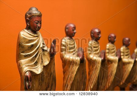 Wooden statues of Buddha with disciples against orange wall.