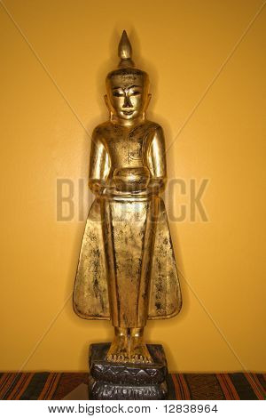 Golden wooden Buddha statue from Myanmar against yellow wall.