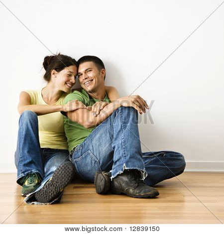 Smiling attractive couple sitting on floor in home.