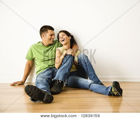 Attractive young adult couple sitting close on hardwood floor in home smiling and laughing.