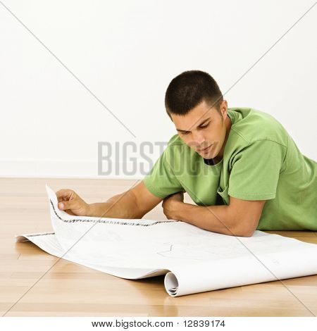 Attractive man lying on floor in home reading house plans.