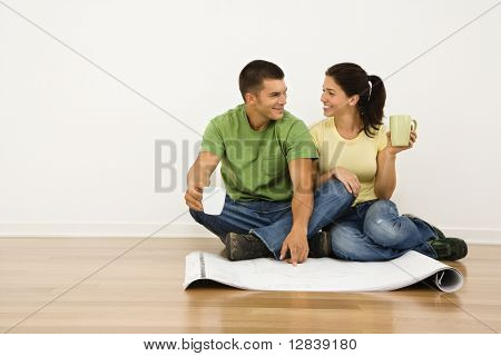 Attractive couple sitting on home floor with coffee cups looking at house plans and smiling at each other.