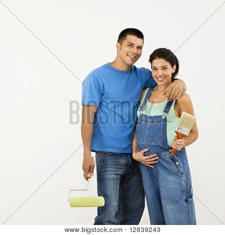 Couple expecting baby holding paintbrushes and smiling.