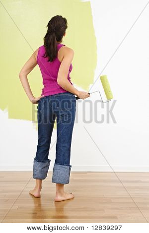 Woman standing holding paint roller admiring partially painted interior wall.