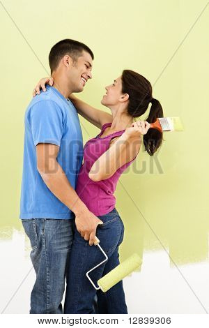 Couple hugging and smiling at each other holding paintbrushes in front of partially painted wall.