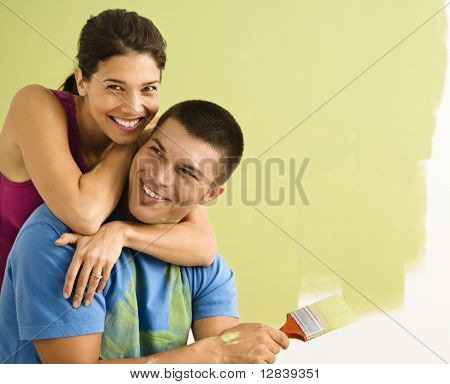 Happy smiling couple painting interior wall of home.