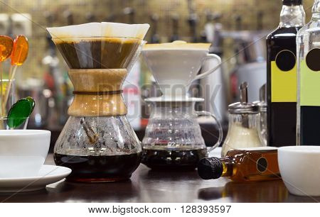 Brew coffee pour-over and chemex on the counter at the coffee shop. The background is blurred.
