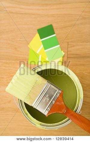 High angle view of paintbrush resting on paint can with color samples.