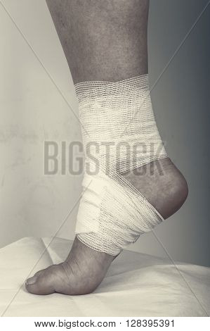 Injured ankle with bandage on a grey background