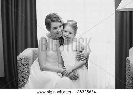 Mother and daughter in the same wedding dresses having fun