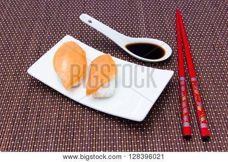 Nigiri with salmon on a bamboo mat