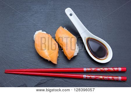 Nigiri with salmon on a slate top seen from above
