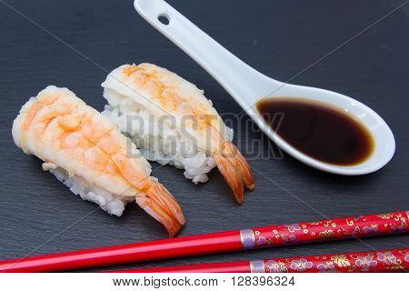 Nigiri with shrimp on a slate floor seen up close