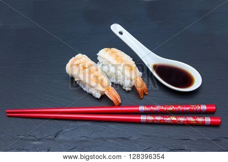 Nigiri with shrimp on a slate floor