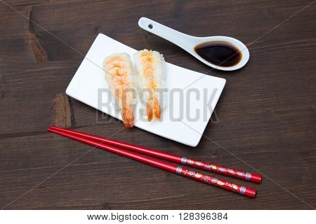 Nigiri with shrimp on a wooden table seen from above