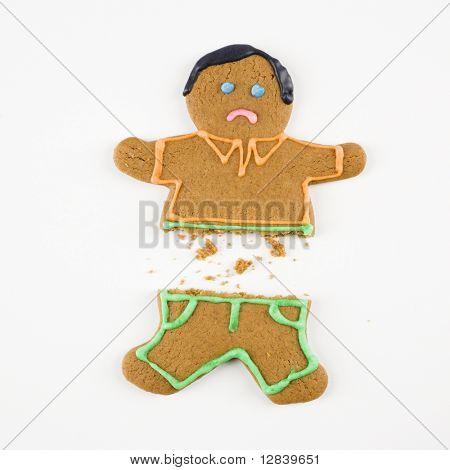 Frowning male gingerbread cookie broken in half.