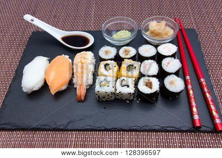 Sushi on flat slate on a bamboo mat