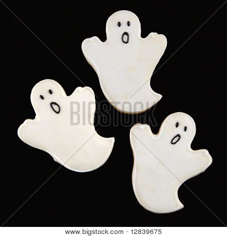 Three sugar cookies in shape of ghosts with decorative icing.