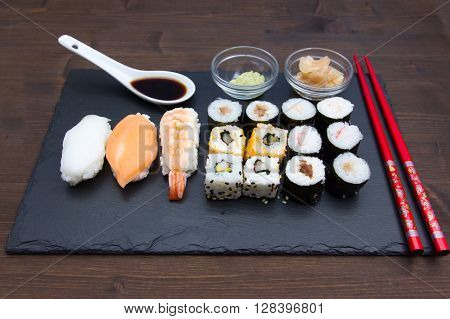 Sushi on flat slate on a wooden table