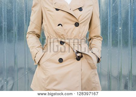 Woman in beige coat outdoors close up