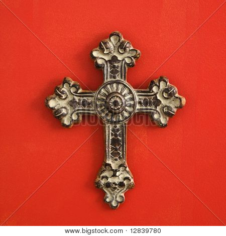 Ornate religious cross hanging on red wall.