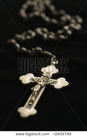 Rosario cristiano con crucifijo sobre fondo negro.