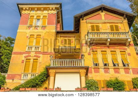 Top and windows of a colorful apartment building in Malcesine, Lake Garda, Italy.