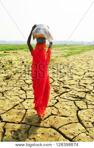 Women carrying baskets on dry ground, India