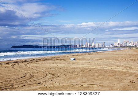 Empty Beach And Litter Bin Against City Skyline