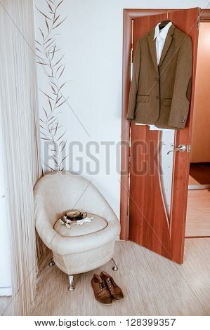groom brown suit brown shoes bow tie belt boutonniere on the background of the home interior