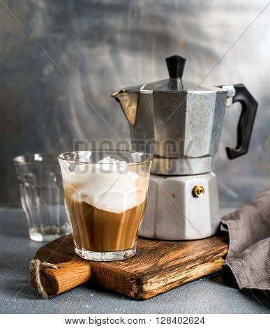 Glass of coffee with ice cream on rustic wooden board and steel Italian Moka pot. Metal background, selectibe focus
