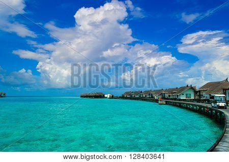 Tropical maldivian island blue lagoon with water villa