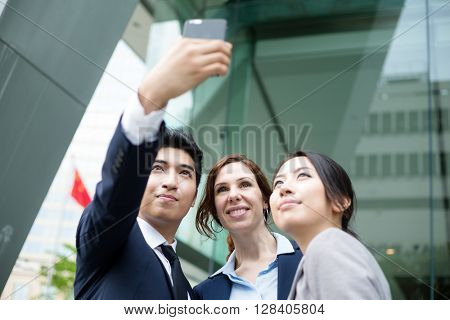 Business people taking self photo together