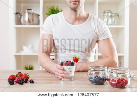 Closeup On Man With Delicious Yoghurt With Fresh Berries