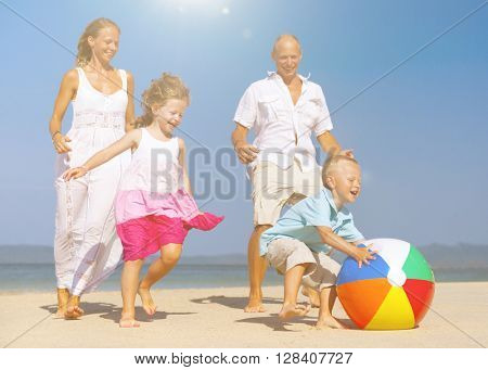 Family playing ball on beach.