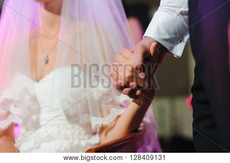 Groom holds the hand of a bride during a wedding ceremony. Bride sits. Wedding dress and veil. A man stands.
