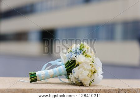 Gentle wedding bouquet on a stone parapet in the background of a modern building. White and blue flowers tied with blue ribbon and white lace.