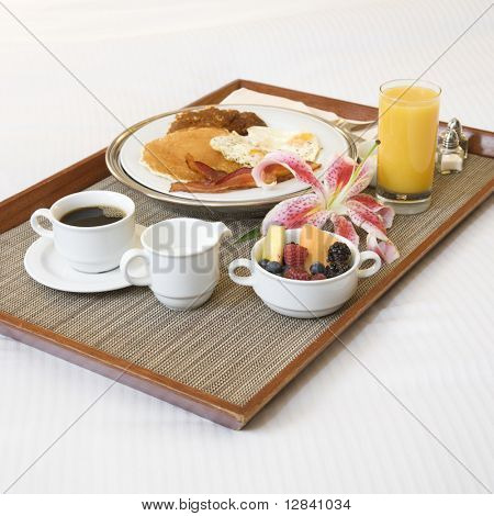 Close-up of breakfast tray laying on white bed.