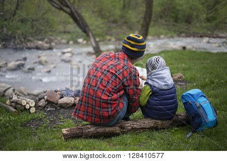 Father And Son Sitting Near A Campfire At The Campsite And Are Looking At The Map.