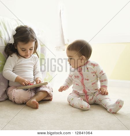 Caucasian girl children sitting on bedroom floor looking at book.