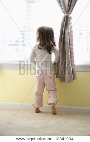 Caucasian girl toddler standing on tip toes looking out of window.