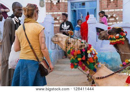 ASWAN, EGYPT - FEBRUARY 5, 2016: Tourist in Nubian village renting camel.