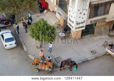 CAIRO, EGYPT - FEBRUARY 2, 2016: Aerial view of street corner with horse cart oranges vendor.