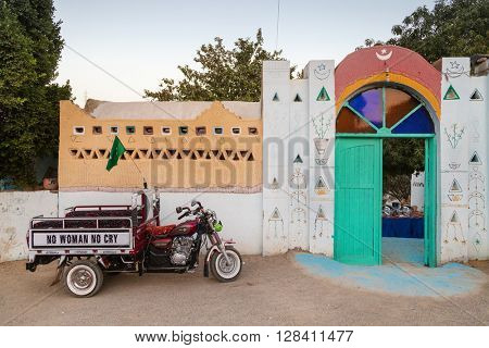 ASWAN, EGYPT - FEBRUARY 5, 2016: Motorcycle with cart parked in front of colorful yard entrance in Nubian village.