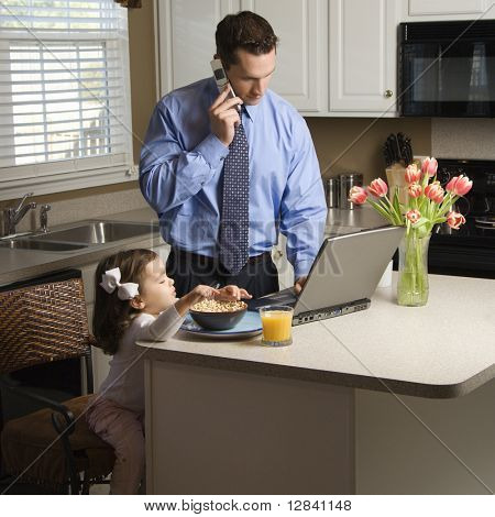 Caucasian father in suit talking on cellphone and using laptop computer with daughter eating breakfast in kitchen.