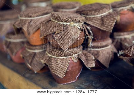 Abkhazia wild honey in Clay pot with cloth  on wooden background ** Note: Shallow depth of field