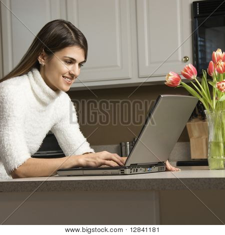 Caucasian woman in kitchen looking at laptop computer.