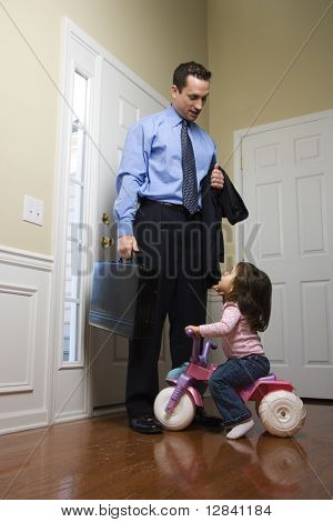 Caucasian businessman at door with briefcase with daughter looking up at him.