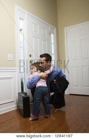 Caucasian Geschäftsmann an Tür mit dem Aktenkoffer knuddeln Tochter.